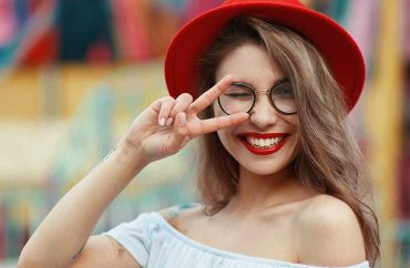 cheerful-girl-winking-and-smiling-while-showing-vi-low